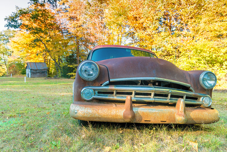 Old car wreck in a countryside field.