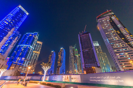 wordwide: DUBAI, UAE - OCTOBER 9, 2015: Dubai Marina night skyline. The city attracts 13 million people wordwide every year.