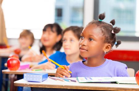 salon de clases: Niños felices en un aula de primaria multi étnica.