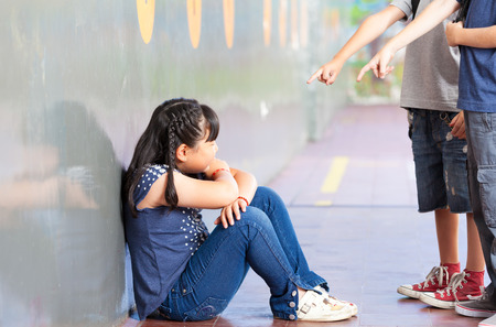 Sad pupil being bullied by classmates at corridor in school.