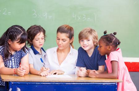 Des enfants heureux dans une salle de classe élémentaire multi-ethnique. Banque d'images - 54116916