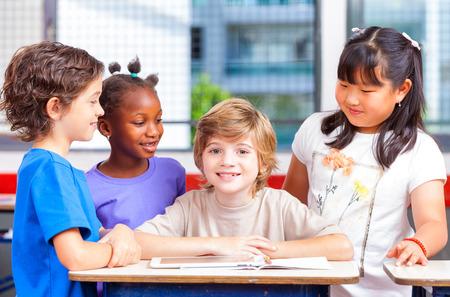 Happy children in a multi ethnic elementary classroom.