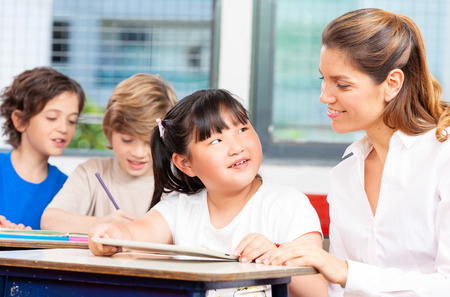 Happy elementary students with teacher. Stock Photo