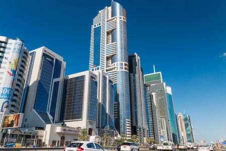 annually: DUBAI - NOVEMBER 22, 2015: City streets on a beautiful day. Dubai attracts 10 million tourists annually.