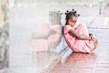 marginalization: School bullying. Isolated girl under rain.