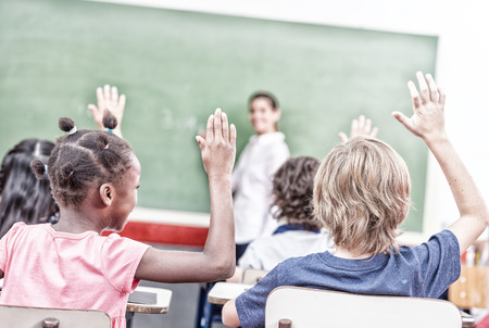 multi race: Raising hand at class lesson, primary school scene. Success and education concept.