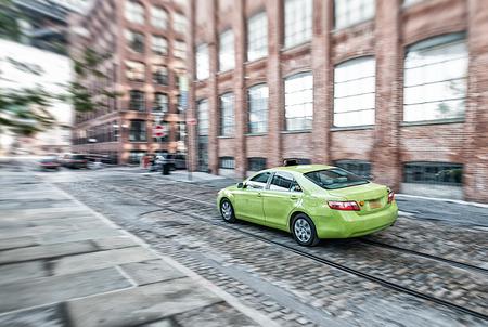 hailing: Green taxi speeding up in Brooklyn, New York City.