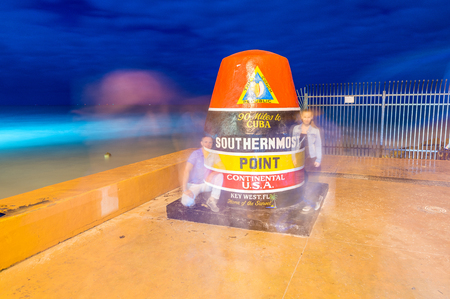 southernmost: KEY WEST, FLORIDA - JANUARY 12, 2016: Tourists take photographs at night in Southernmost Point. Key West is a famous tourist attraction in Florida.
