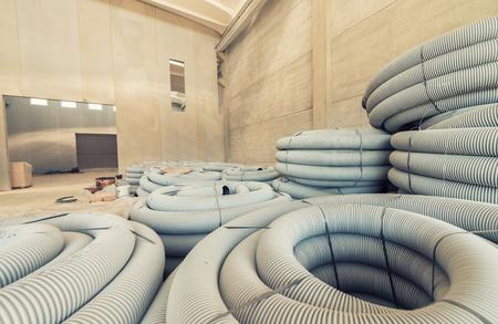 plastic pipe: Grey plastic corrugated pipe inside a warehouse.