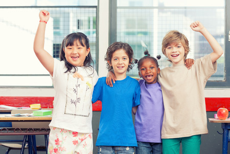 multi race: Happy children at school. Multi race classroom enjoying life. Integration concept.