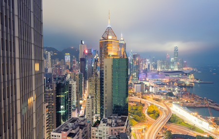 urban scene: HONG KONG - APRIL 7, 2014: Hong Kong night skyline. The city attracts more than 30 million people annually.