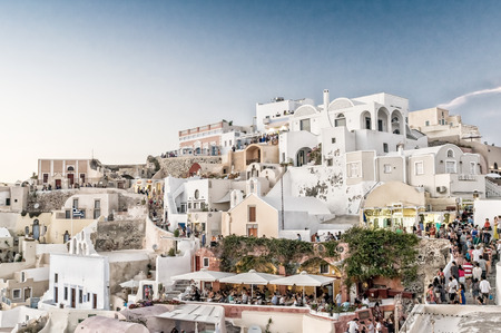 OIA, GREECE - MAY 12, 2014: Tourists await the famous sunset in Santorini. The island a a famous summer tourist destination.