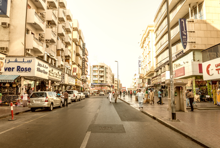 annually: DUBAI - OCTOBER 21, 2015: Street of Deira area on a sunny day. Dubai attracts 15 million visitors annually.