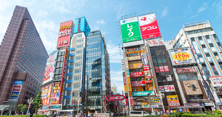 administrative buildings: TOKYO - JUNE 1, 2016: Buildings and ads of Shinkuku near railway station. It is a major commercial and administrative centre, housing the busiest railway station in the world.