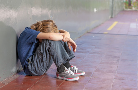 Schoolboy sitting on floor at school. Bullying and isolation concept.