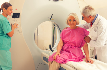 Old female patient undergoing mri in hospital assisted by doctors.