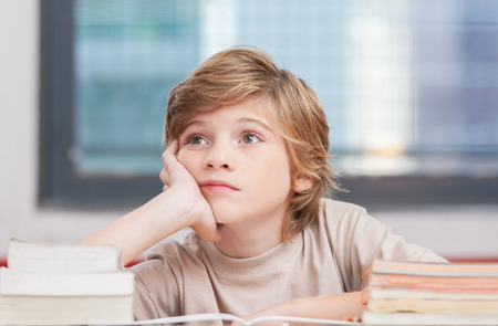 Schoolboy thinking with his books in classroom.