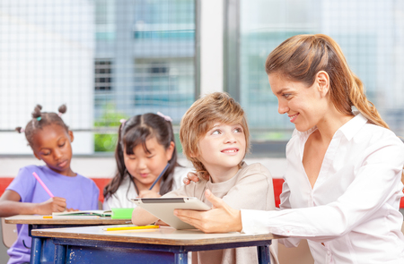 beautiful teacher: Beautiful teacher with mixed race classroom.