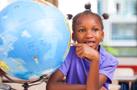 African girl at school with earth globe in background, geography and education concept. Stock Photo