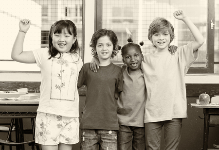 classmates: Happy multi ethnic classmates hugging at primary school. Stock Photo