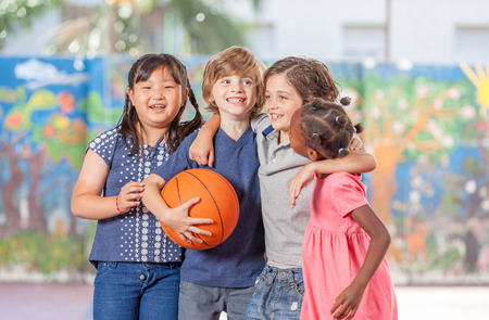 mixed race children: Group of mixed race children playing basketball in school courtyard. Stock Photo