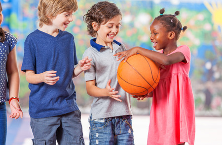multi race: Multi race schoolmates playing basketball. Stock Photo