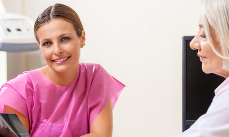 hospital patient: Happy female patient looking at hospital test results. Stock Photo
