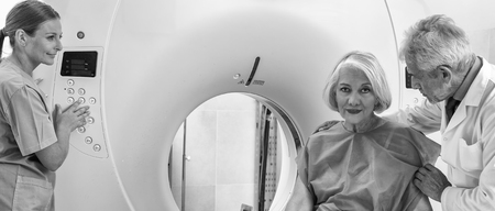 assisted: Old female patient undergoing mri in hospital assisted by doctors.