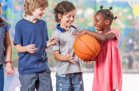 Mixed race classmates playing in schoolyard.