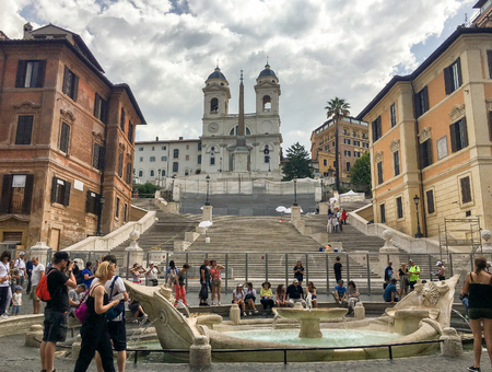 fontana: ROME - JULY 2016: Tourists visiting the Piazza di Spagna (Spanish square), the Spanish Steps and the Fontana della Barcaccia in Rome.