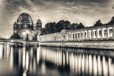 dom: Berlin Cathedral at night with Spree river reflections of columns.