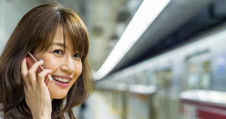 Smiling beautiful asian girl answering phone call inside a subway station.