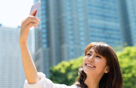 happy asian people: Beautiful asian girl making selfie in city center. Stock Photo