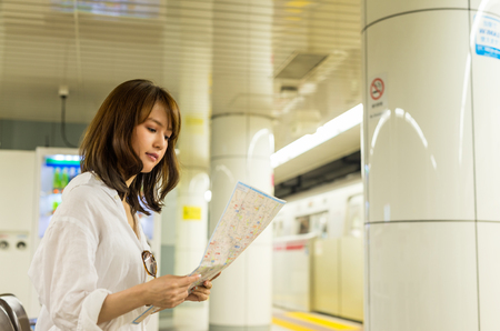 happy asian people: Asian girl consulting city map inside subway station. Stock Photo