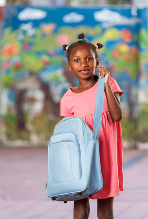 schoolyard: Cheerful african girl in schoolyard with her handbag. Stock Photo