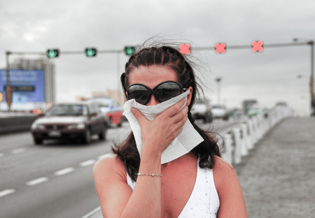 Woman fighting smog along city streets.