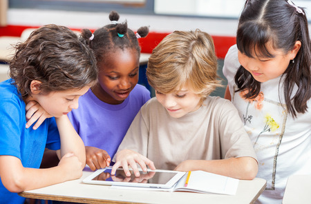 Multi ethnic classroom learning use of tablet.