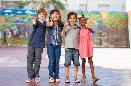 Elementary multi ethnic class children embracing happy at school.