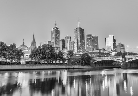 annually: MELBOURNE - OCTOBER 2015: Black and white city skyline at night. The city attracts 10 million tourists annually. Editorial