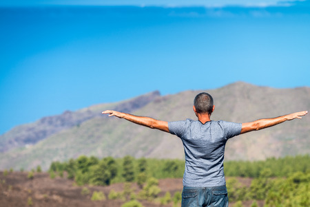 Happy man with arms open enjoying mountain scenario. Back view. photo