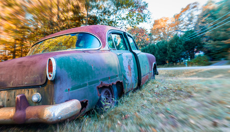 abandoned car: Abandoned car rusting in a field.
