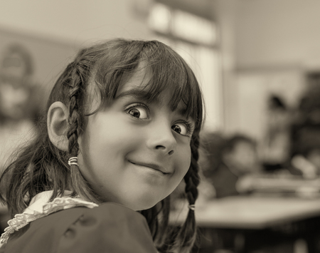 Funny face of a schoolgirl in elementary classroom. photo