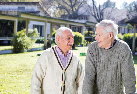 rehab: Happy retired men talking outdoor in a rehab facility garden. Stock Photo