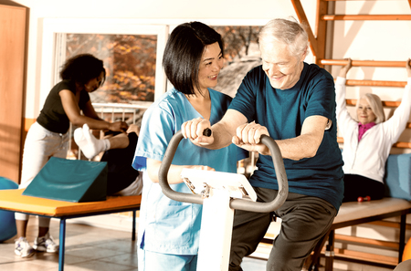 Elder retired woman assisted by nurse in rehab facility. Stock Photo