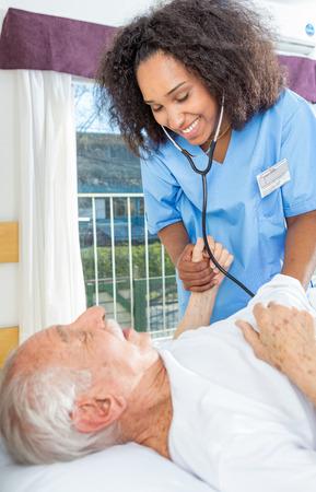 Elder hombre se retiró con la asistencia de la enfermera en la clínica de rehabilitación. Foto de archivo