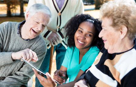 看護師は、高齢者にタブレットの使用を説明します。