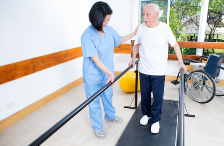 rehab: Elder retired man assisted by nurse in rehab clinic. Stock Photo