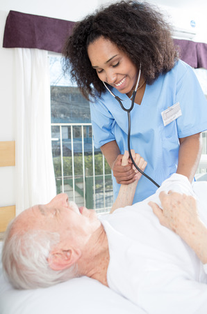 healthcare facility: Elder retired man assisted by nurse in rehab clinic. Stock Photo