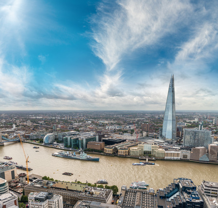 shard: London, UK. Aerial view of buildings along river Thames at sunset.