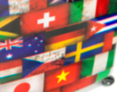 International flags printed on a luggage. Tourism concept, blurred view.